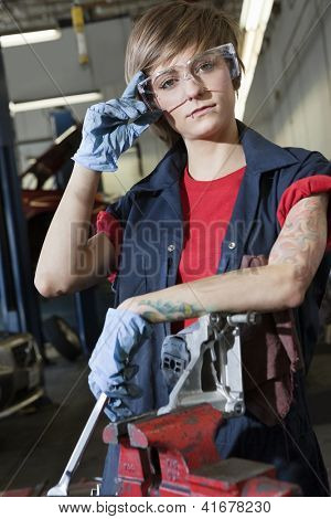Portrait of a young female mechanic wearing protective eyewear in garage