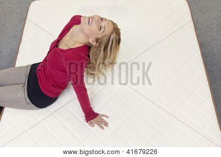 Happy Woman relaxing on Matratze mit Kopf im Möbelhaus