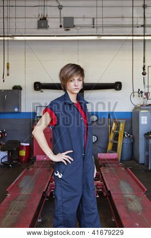 Young female mechanic standing with hand on hip in car workshop