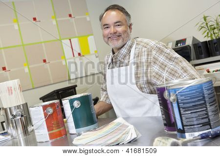 Portrait of a happy middle-aged sales clerk at counter with paint cans in hardware store