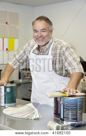 Portrait of a cheerful middle-aged store clerk with paint cans and brush in hardware shop
