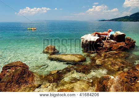 Young girl is sunbathing on a rocky beach in Croatia