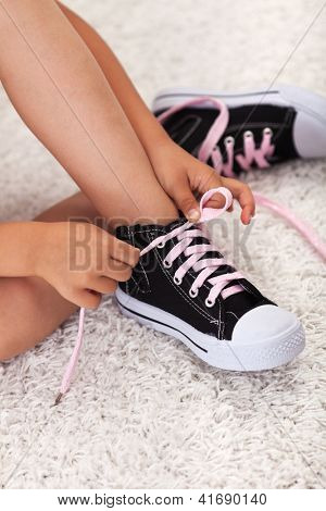 Child hands tie shoelaces - closeup