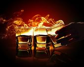 pic of absinthe  - Hand holding one of three glasses of yellow absinth with fume going out - JPG