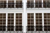 stock photo of scrollwork  - Rows of tall white windows with black wrought - JPG