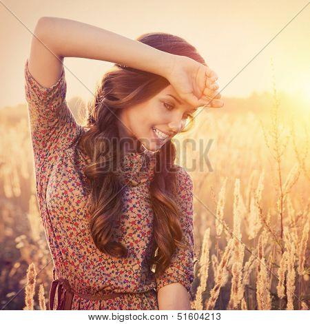 Beauty Romantic Girl Outdoors. Beautiful Teenage Model girl Dressed in Fashionable Short Dress Posing on the Field in Sun Light. Glow Sun. Autumn. Toned in warm colors.