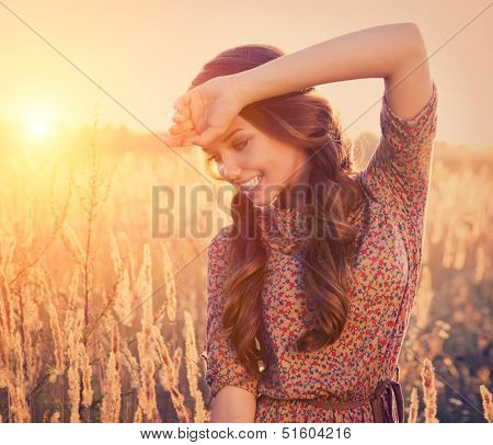 Beauty Romantic Girl Outdoors. Beautiful Teenage Model girl Dressed in Fashionable Short Dress Posing on the Field in Sun Light. Glow Sun. Autumn. Toned in warm colors.