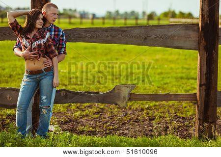 couple on the farm stading near fence