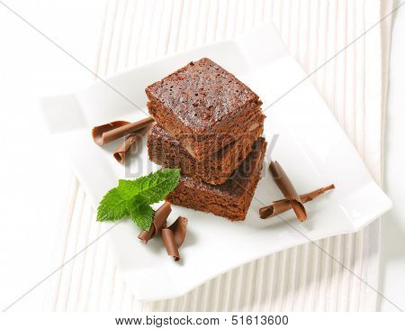 three pieces of smooth brownies with chocolate curls on a square plate