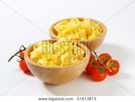 two bowl of boiled tagliatelle with fresh tomatoes