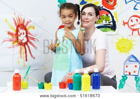 Teacher And Pupil In Pre School Art Class