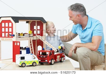 Teacher And Pupil Playing With Wooden Fire Station