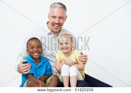 Studio Portrait Of Male Pre School Teacher With Pupils