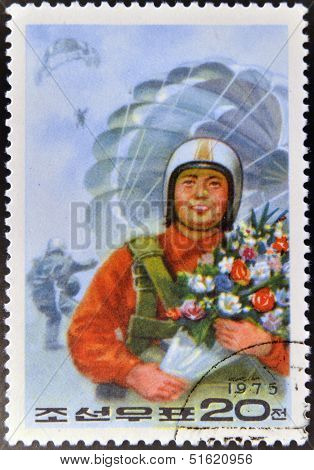 A stamp printed in North Korea shows skydiver with bouquet of flowers