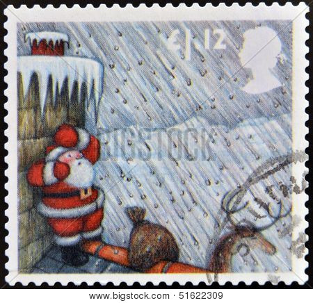 A stamp printed in Great Britain shows image of Santa Claus Sheltering from Hailstorm behind Chimney