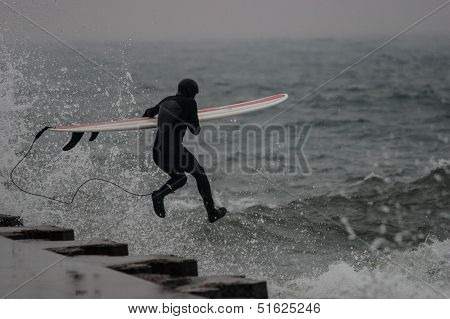 surfers on a pier