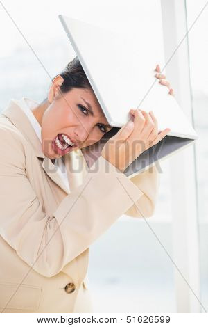 Crazed businesswoman hitting head off laptop looking at camera in her office