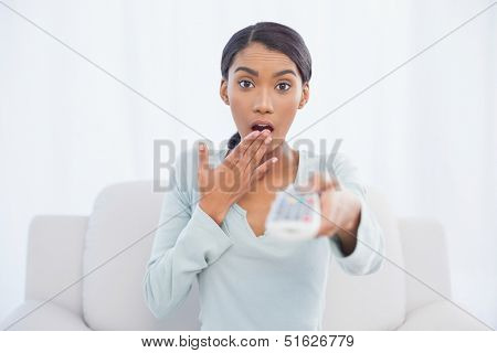 Shocked cute woman sitting on sofa in bright living room changing tv channel