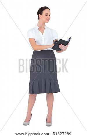 Focused businesswoman writing on her datebook on white background
