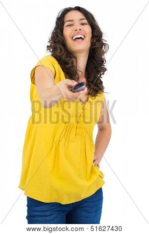Cheerful curly haired pretty woman on white background changing channel with remote