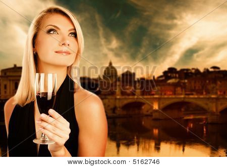 Beautiful woman drinking wine near the river