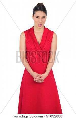 Elegant model in red dress on white background sticking her tongue out