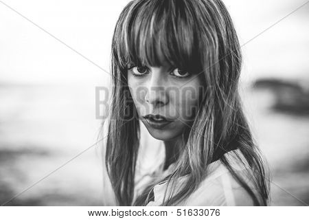 Vulnerable model with fringe staring at camera in black and white artistic shot