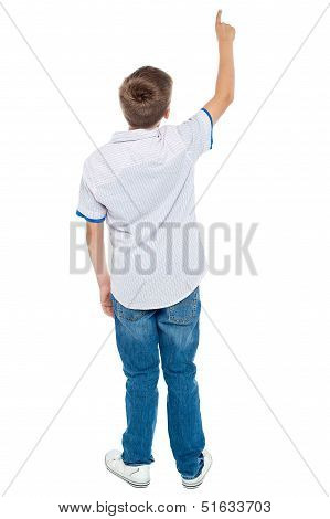 Rear View Of A School Boy Pointing Upwards