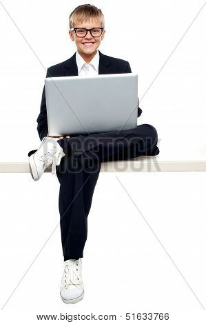 Smartly Dressed Young Kid Working On A Laptop