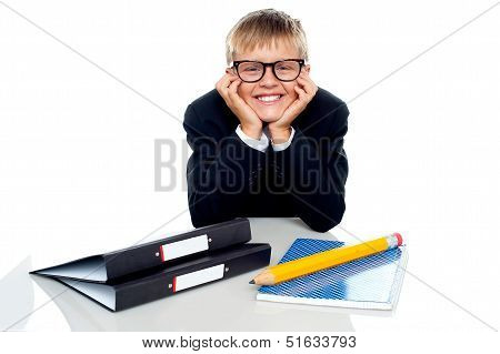 Bespectacled Boy Posing With Files On His Desk