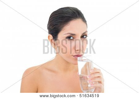 Happy brunette sipping glass of water and looking at camera on white background
