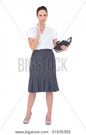 Thoughtful businesswoman holding her datebook on white background