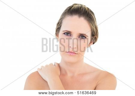 Disgruntled woman looking at camera with a sore shoulder against white background