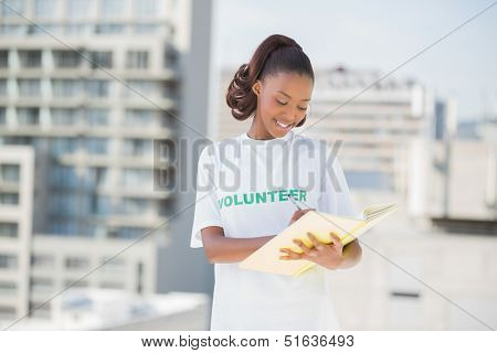 Happy altruist woman writing on notebook outdoors on urban background