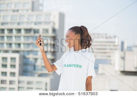 Cheerful altruist woman looking at her mobile phone outdoors on urban background