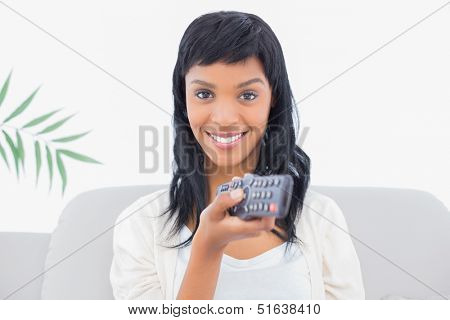 Playful black haired woman in white clothes changing tv channel in a living room