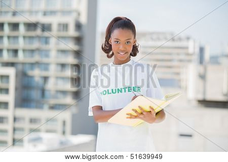 Happy altruist woman holding notebook outdoors on urban background