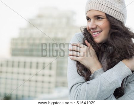 Cheerful pretty young brunette shivering outside on a cloudy day