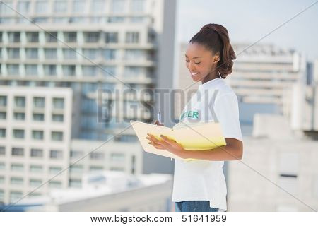 Smiling altruist woman holding notebook outdoors on urban background