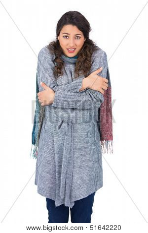 Uneasy pretty model with winter clothes being cold on white background