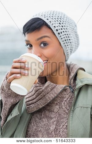 Pleased young model in winter clothes enjoying coffee outside on a cloudy day