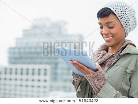 Natural young model in winter clothes using a tablet pc outside on a cloudy day