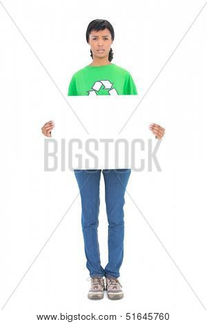 Frowning black haired ecologist holding a white panel in front of her on white background