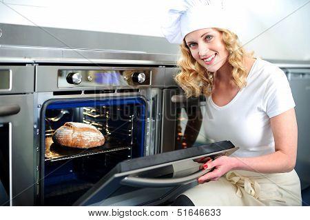 Pretty Baker Opening An Oven Door
