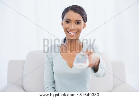 Cheerful cute woman sitting on sofa in bright living room changing tv channel