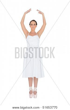 Focused young ballet dancer standing on her tiptoes on white background