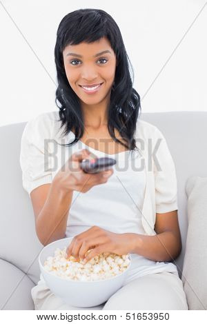 Seductive black haired woman in white clothes changing tv channel and eating popcorn in a living room