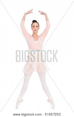 Focused attractive ballerina standing on her tiptoes on white background