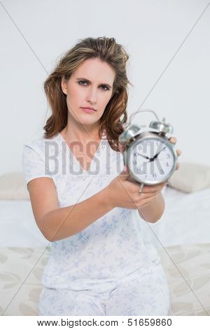 Frowning tired woman in bright bedroom showing alarm clock