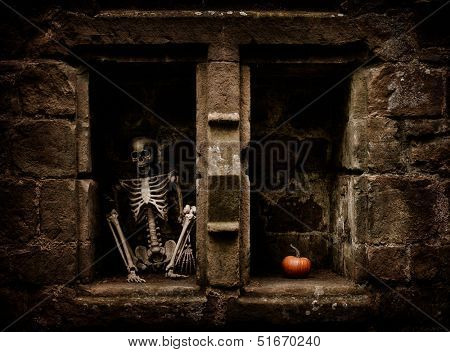 Halloween skeleton sitting in a graveyard alcove